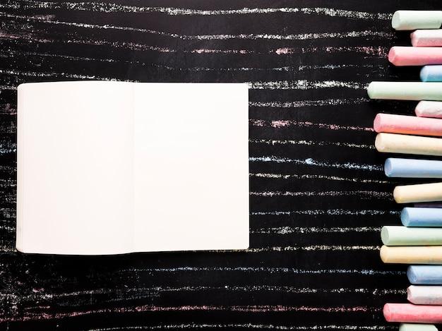 Notizblock mit kreide auf schwarzem brett