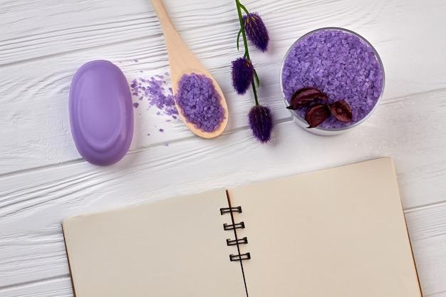 Notizblock mit lila spa-sachen auf weißem holztisch