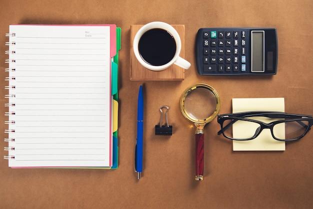 Notizblock mit lupe und taschenrechner mit kaffee auf dem tisch
