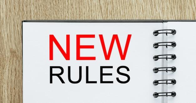Notizblock mit neuen textregeln auf holzschreibtisch. geschäfts- und finanzkonzept