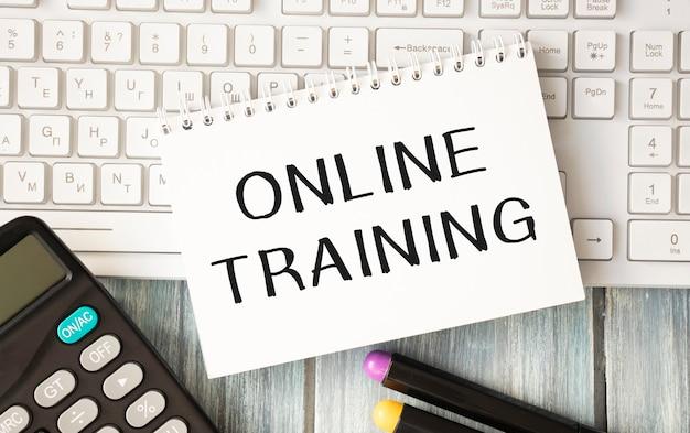 Notizblock mit online-trainingstext auf tastatur auf hölzernem hintergrund