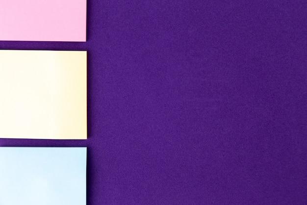 Notizblock mit satz bunten büroklammern auf purpur