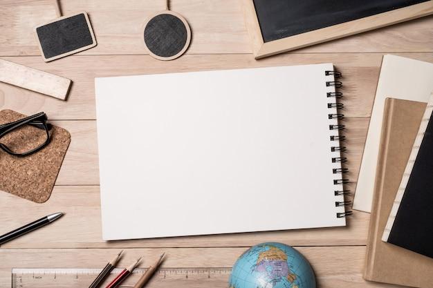 Notizblock mit schulmaterial, globus, notizbuch und tafel auf einem holztisch.