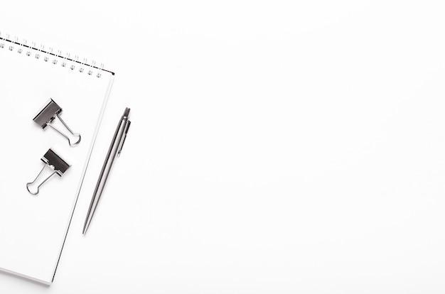 Notizblock mit silbernem briefpapier, stift auf weißem hintergrund. office-desktop. kopierraum, draufsicht, flache lage