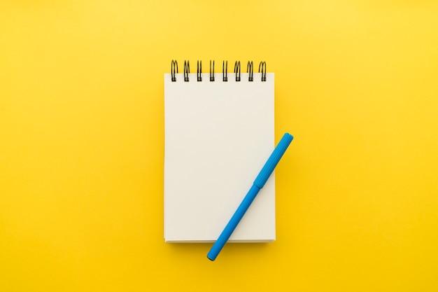 Notizblock mit stift auf gelbem hintergrund