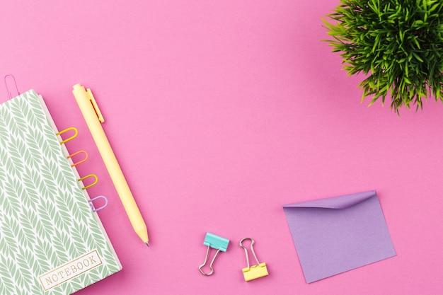 Notizblock mit stift auf rosa hintergrund