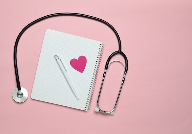 Notizblock mit stift, dekorativem herzen, stethoskop auf rosa pastellhintergrund, medizinisches konzept, draufsicht, minimalismus-trend