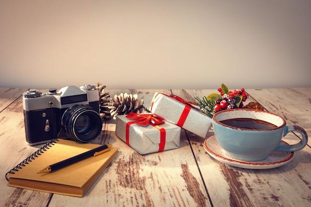 Notizblock mit stift, retro-fotokamera, geschenken und kaffee auf holzoberfläche