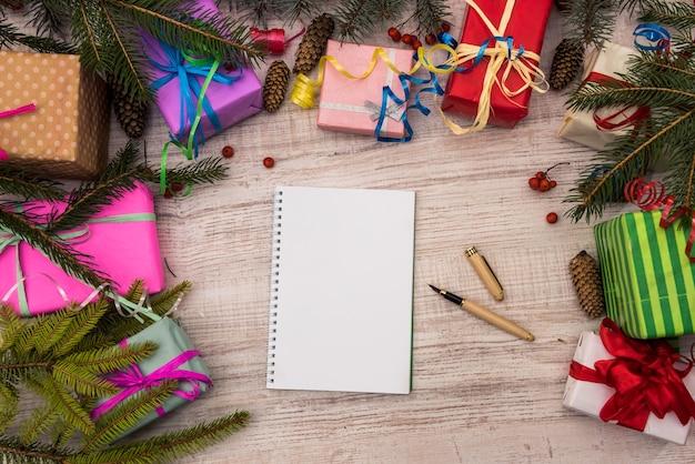 Notizblock mit stift und bunten geschenkboxen auf holztisch. feier und geschenke