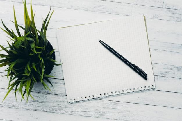 Notizblock mit stiftblume eingetopftem holztischbüro-draufsicht