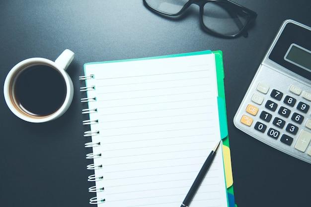 Notizblock mit taschenrechner auf dem schreibtisch