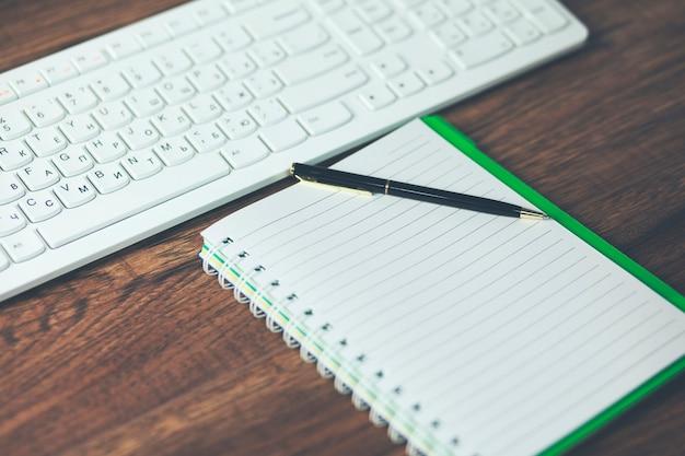 Notizblock mit tastatur auf holzschreibtisch