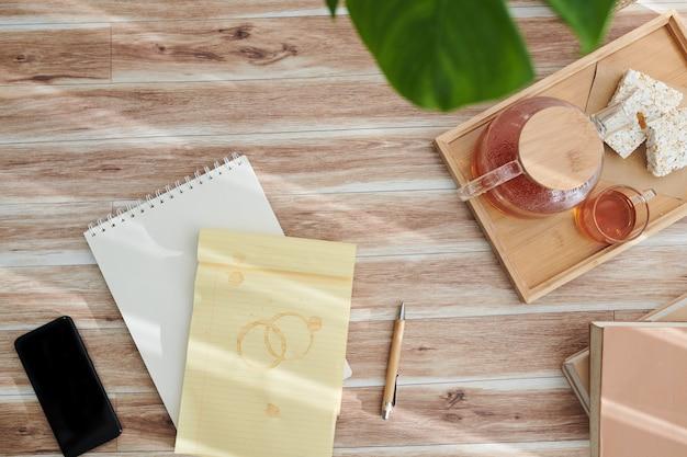 Notizblock mit teeflecken und tablett mit kanne und tassen auf dem schreibtisch der kreativen person, ansicht von oben