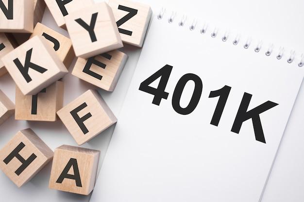 Notizblock mit text 401k und holzwürfel mit buchstaben