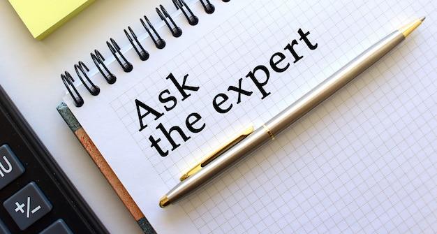 Notizblock mit text ask the expert, daneben liegen ein taschenrechner und gelbe notizpapiere. unternehmenskonzept.