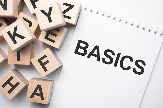Notizblock mit text basics und holzwürfel mit buchstaben