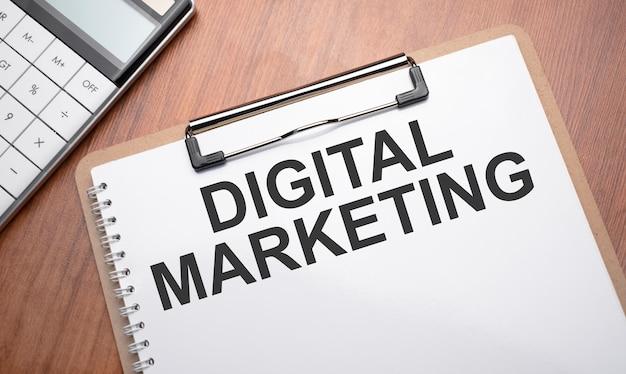 Notizblock mit text digitales marketing auf holzuntergrund mit clips, stift und taschenrechner