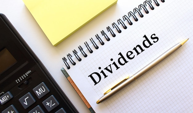 Notizblock mit text dividends, daneben ein taschenrechner und gelbe notizpapiere.