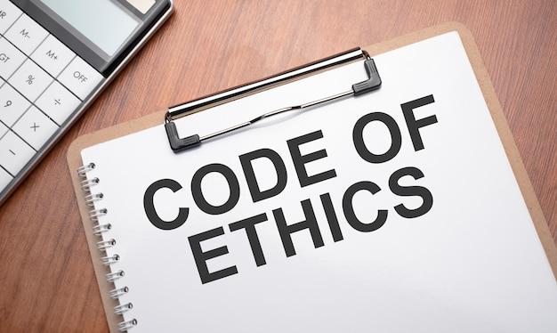 Notizblock mit text-ethik-code auf holzhintergrund mit clips, stift und taschenrechner