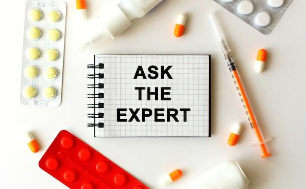 Notizblock mit text fragen sie den experten auf einem weißen tisch. in der nähe befinden sich verschiedene medikamente. medizinisches konzept.