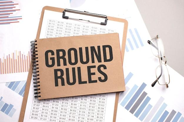 Notizblock mit text grundregeln auf diagrammen und zahlen. geschäftskonzept.