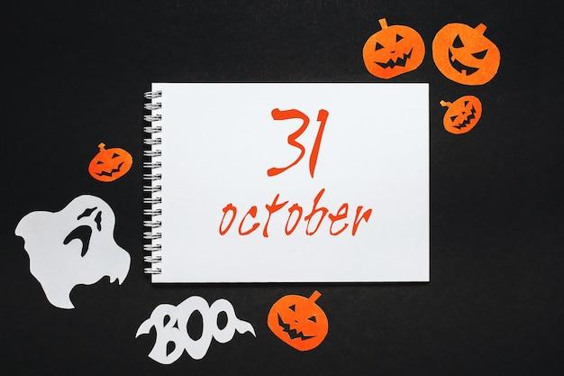 Notizblock mit text halloween auf schwarzem hintergrund
