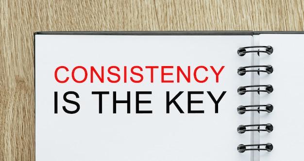 Notizblock mit text konsistenz ist der schlüssel zum schreibtisch aus holz. geschäfts- und finanzkonzept