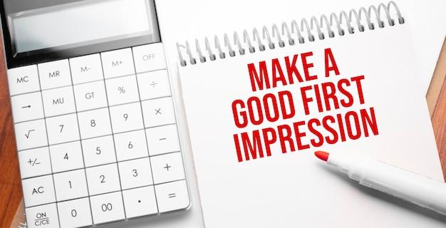 Notizblock mit text machen sie einen guten ersten eindruck auf holzuntergrund mit taschenrechner und rotem marker