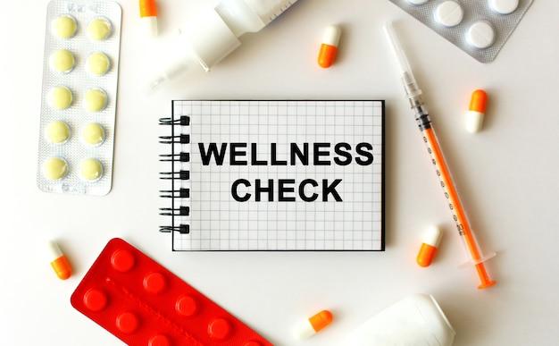 Notizblock mit text wellness check auf einem weißen tisch. in der nähe befinden sich verschiedene medikamente. medizinisches konzept.