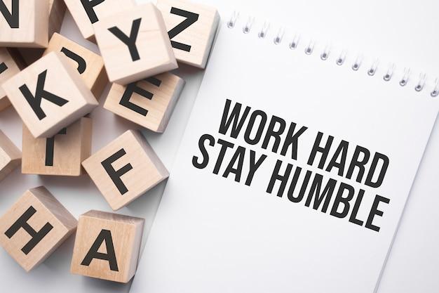 Notizblock mit text work hard stay humble und holzwürfeln mit buchstaben