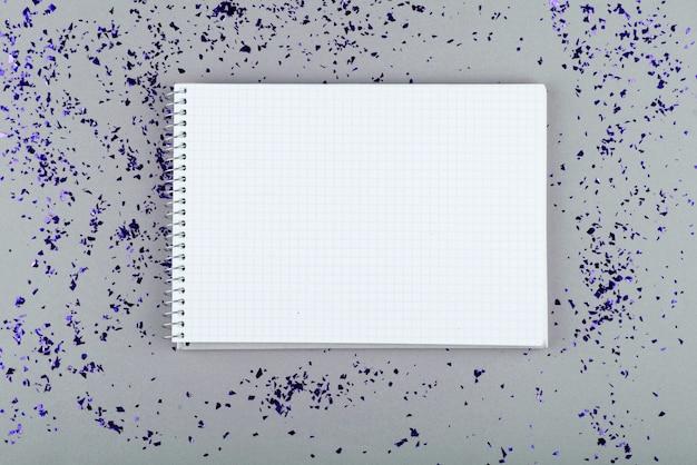 Notizblock mit weißen blättern und stift auf einem grauen hintergrund