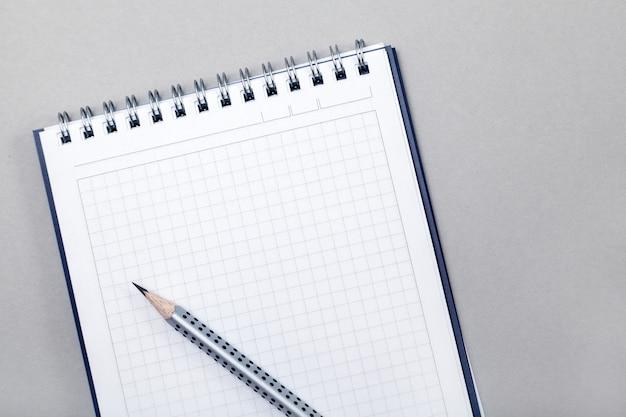 Notizblock oder notizbuch mit bleistift auf grau