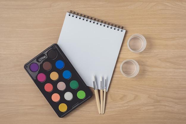 Notizblock oder notizbuch mit malerpinsel- und aquarellpalette auf brauner hölzerner tabelle unter verwendung für künste und bildung