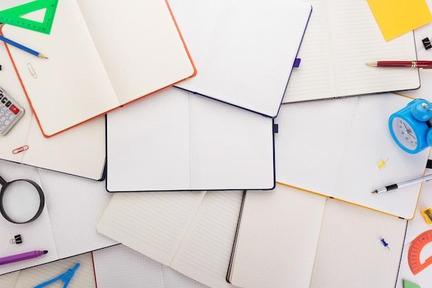 Notizblock oder notizbuch mit schulmaterial, ansicht von oben