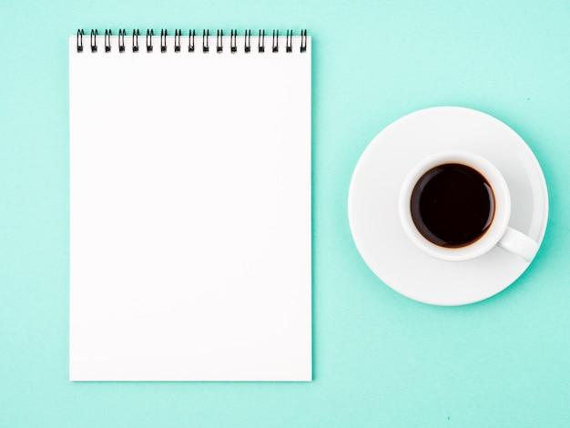 Notizblock offen mit weißer leerseite für das schreiben der idee oder der aufgabenliste, tasse kaffee auf blauem hintergrund