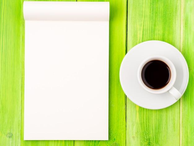 Notizblock offen mit weißer leerseite für das schreiben von idee oder von aufgabenliste, tasse kaffee auf grüner hölzerner tabelle
