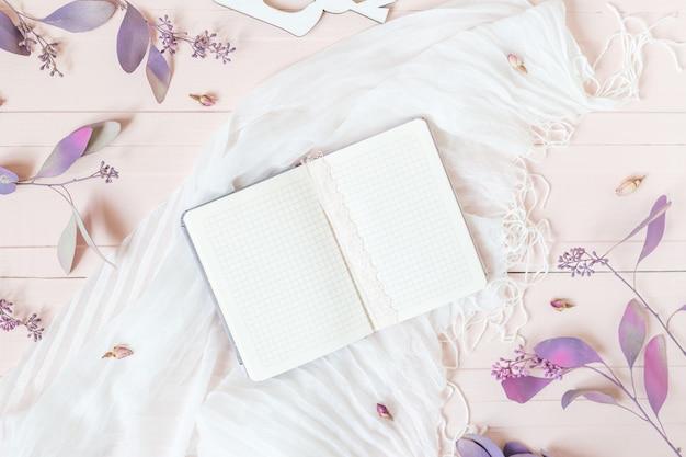 Notizblock, rosa blumen und eukalyptusblätter auf einer rosa tabelle. top wiev