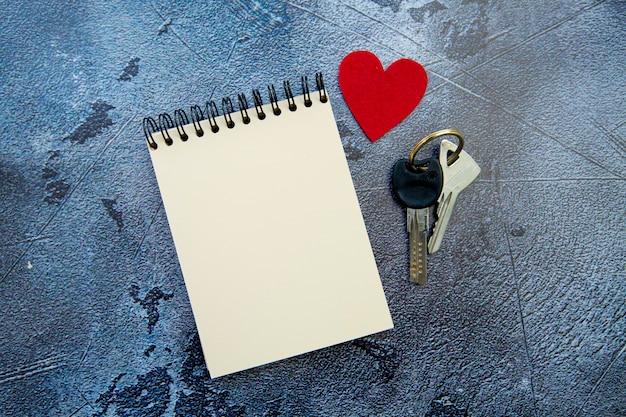 Notizblock, rote herz- und valentinstaggeschenkschlüssel auf grauem hintergrund
