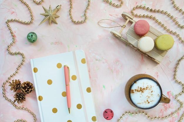 Notizblock, stift, kaffee, makronen und dekoration. weihnachtsarbeitsplatz