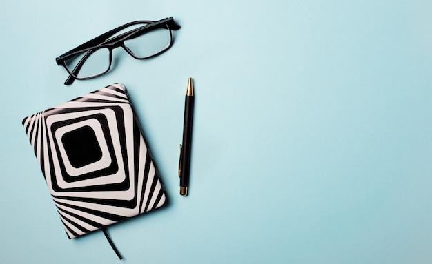 Notizblock, stift und brille auf hellblau. speicherplatz kopieren