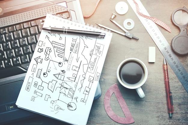 Notizblock über laptop und kaffee auf holztisch