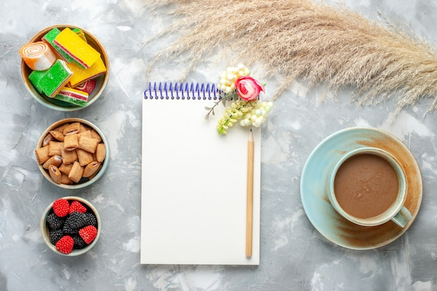 Notizblock und bonbons der draufsicht mit keksen zusammen mit milchkaffee auf leichtem schreibtischkuchenkekskuchen süßem zucker