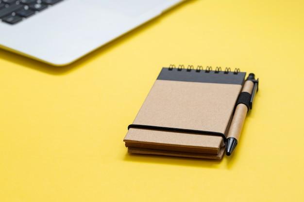 Notizblock und computer auf gelbem hintergrund