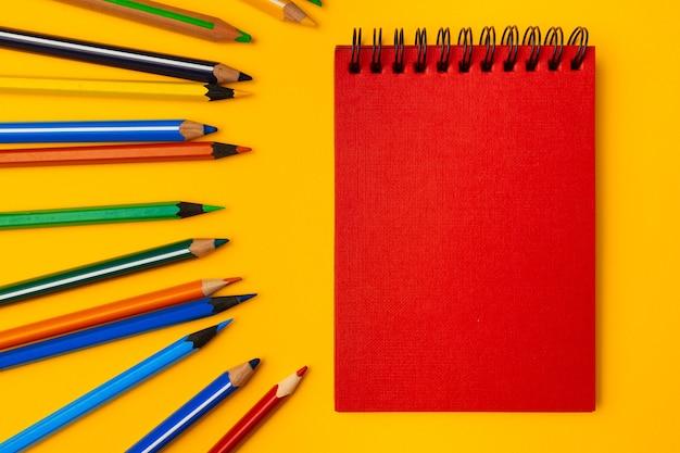 Notizblock und farbstifte auf gelbem hintergrund