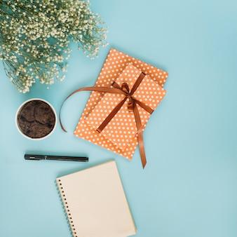 Notizblock und geschenk nahe kleinem kuchen und blumenstrauß