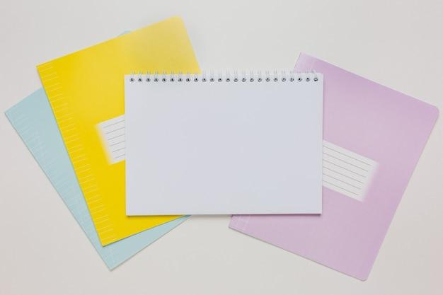 Notizblock und heft auf dem schreibtisch. mock-up im kopierraumbüro auf weißem hintergrund. zurück zur schule