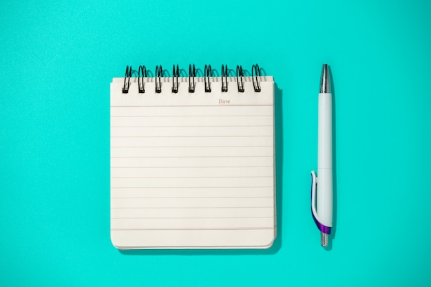 Notizblock und stift auf blauem tisch