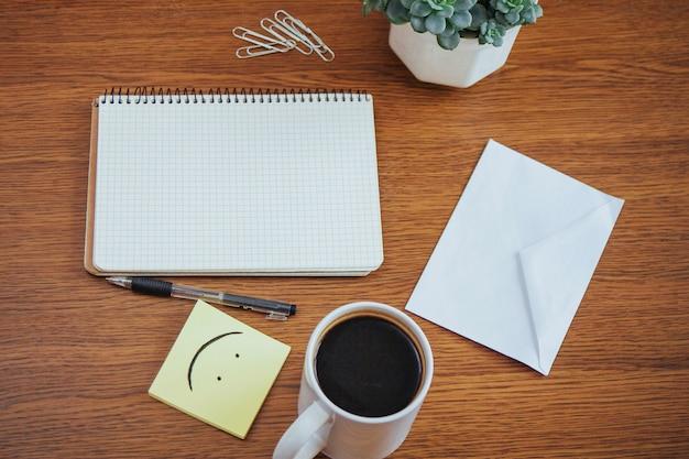 Notizblock und stift neben einem tasse kaffee auf einem holztisch draußen an einem café.