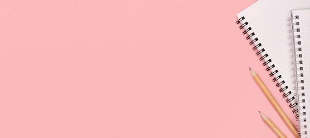Notizblock und stifte auf rosa. speicherplatz kopieren.