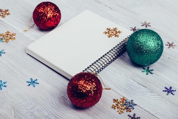 Notizblock, weihnachtsbälle und schneeflocken auf einer weißen tabelle
